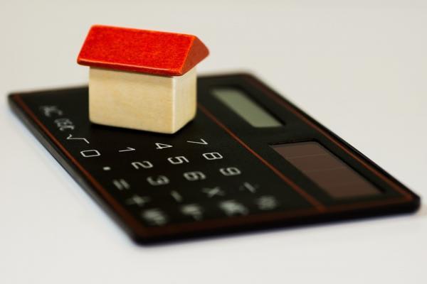電卓の上に載っている家の模型
