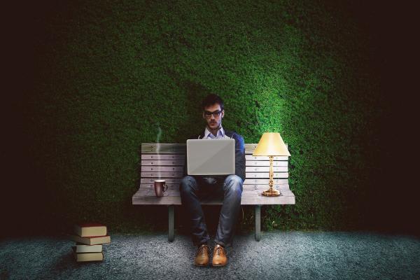 ベンチでパソコンを触る男性