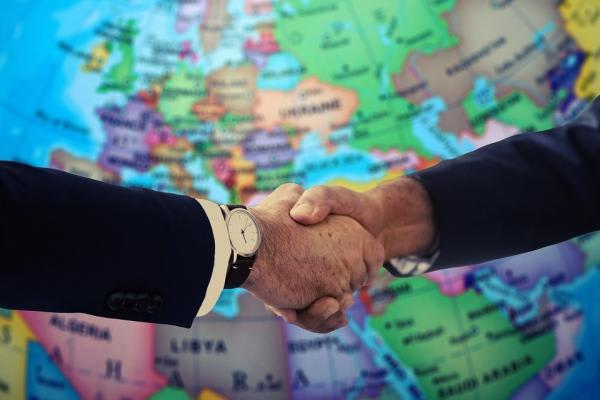 地球儀の前で握手する手元の様子