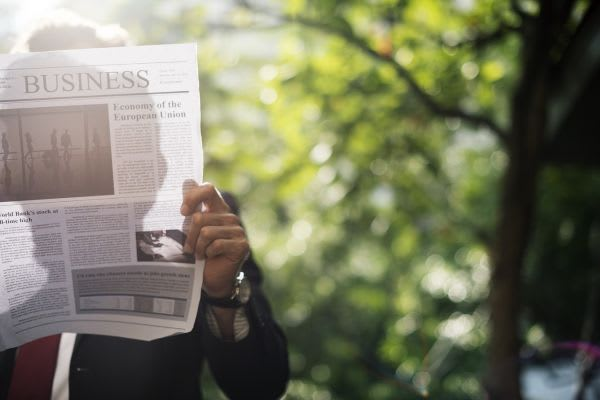 新聞で情報を集めている画像
