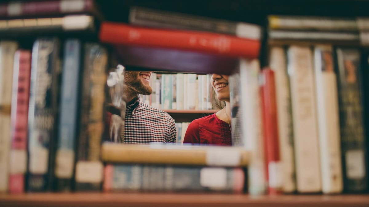 A man and a woman smiling at each other in a library.