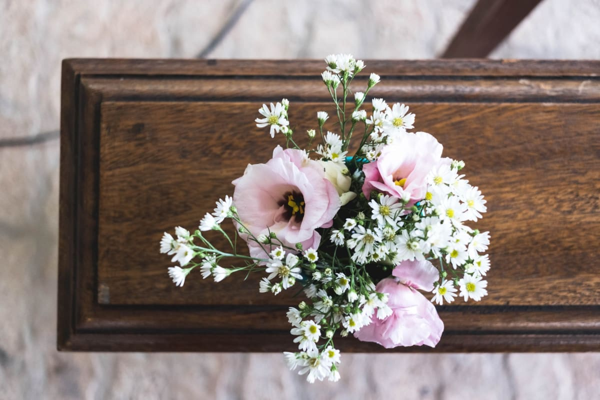 Flowers sit on a bench at a funeral during the coronavirus outbreak