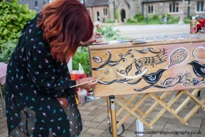 A woman decorates a coffin supplied by A Natural Undertaking