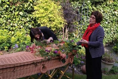 People decorating their loved one's coffins