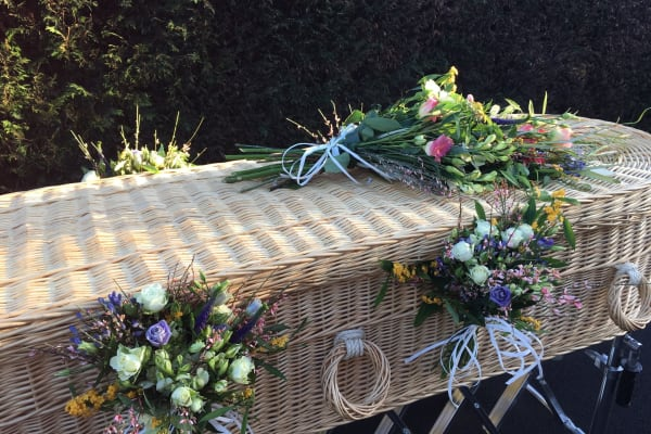 A wicker coffin decorated with flowers by the team at Full Circle Funerals