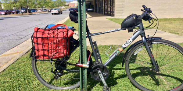 A photo of a parked bicycle with baskets full of groceries.