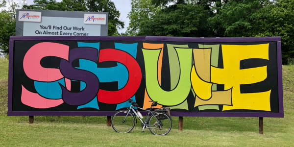 """A photo of my bicycle in front of a billboard mural with the words """"SOUL SHINE"""" in stylized lettering."""