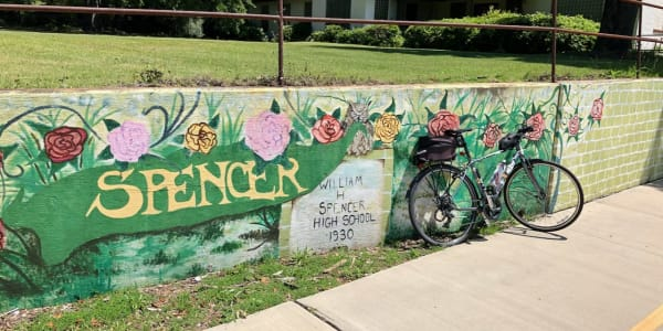 A photo of a bicycle in front of a public mural.