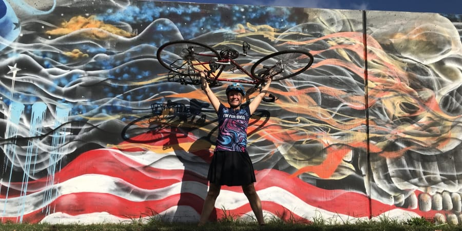 A photograph of Pattie Baker holding her bicycle in front of a mural.