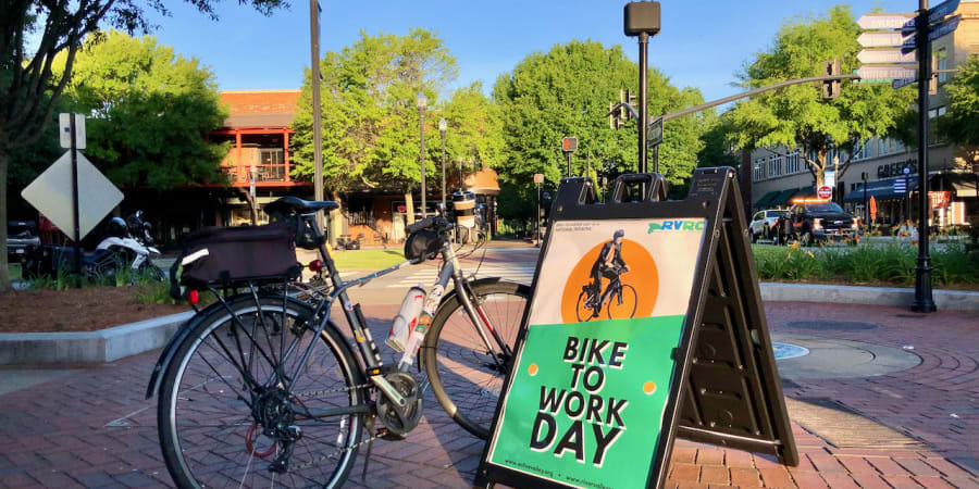 """A photo of a bicycle beside a sign saying """"BIKE TO WORK DAY."""""""