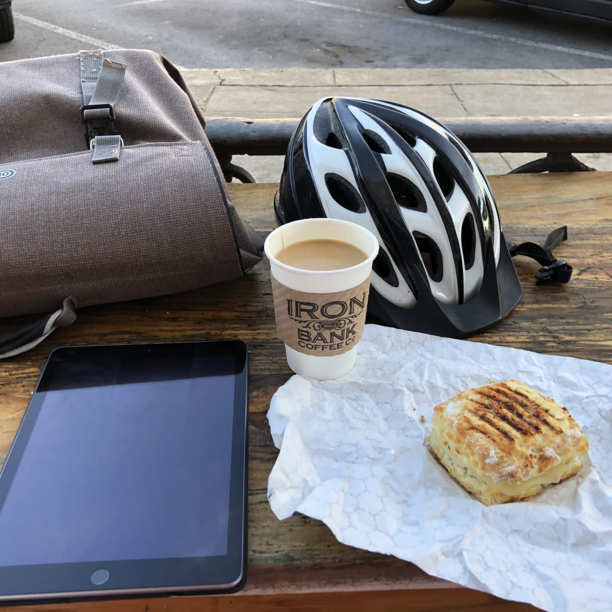 A photo of my bag, helmet, iPad, and coffee on an outdoor table.