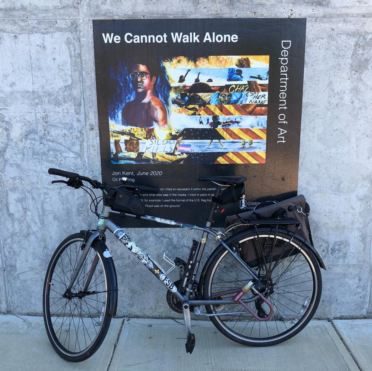 """A photo of my bicycle in front of an art piece titled """"We Cannot Walk Alone."""""""
