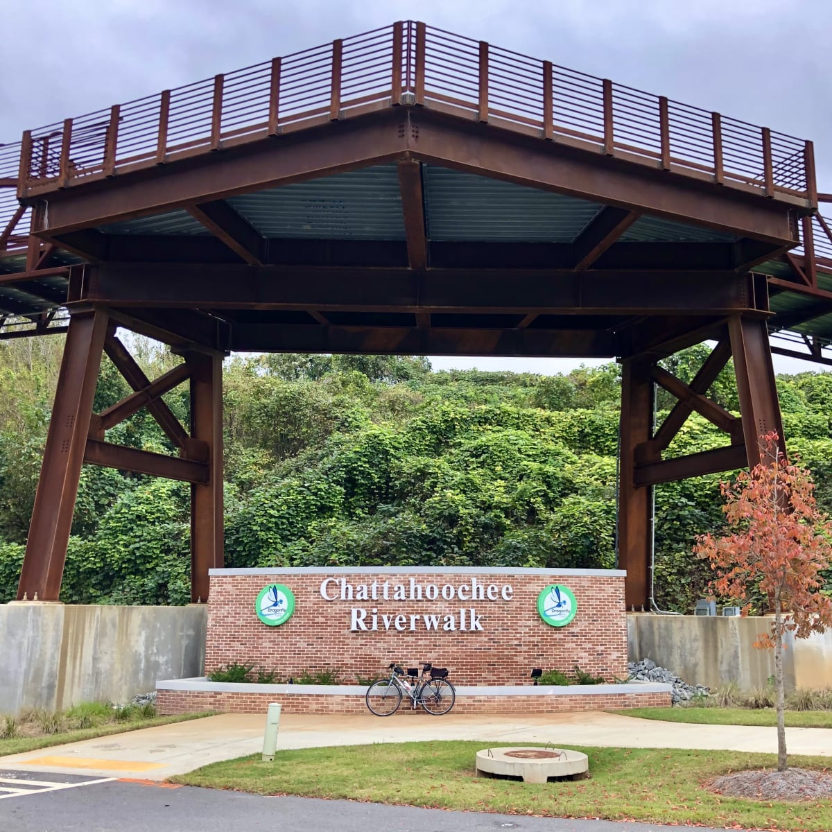 """A photo of my bicycle in front of a sign for """"Chattahoochee Riverwalk"""" and under a pedestrian bridge."""