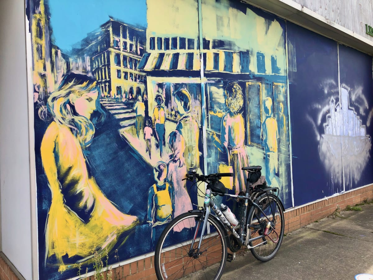 A photo of my bicycle in front of a mural with a painting of a public scene.
