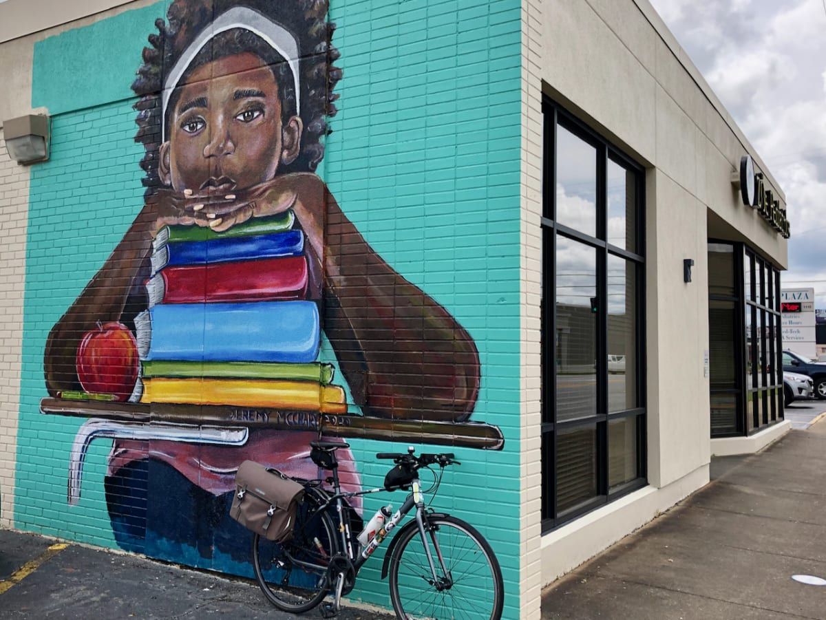 A photo of my bicycle in front of a mural with a painting of a student in a desk.