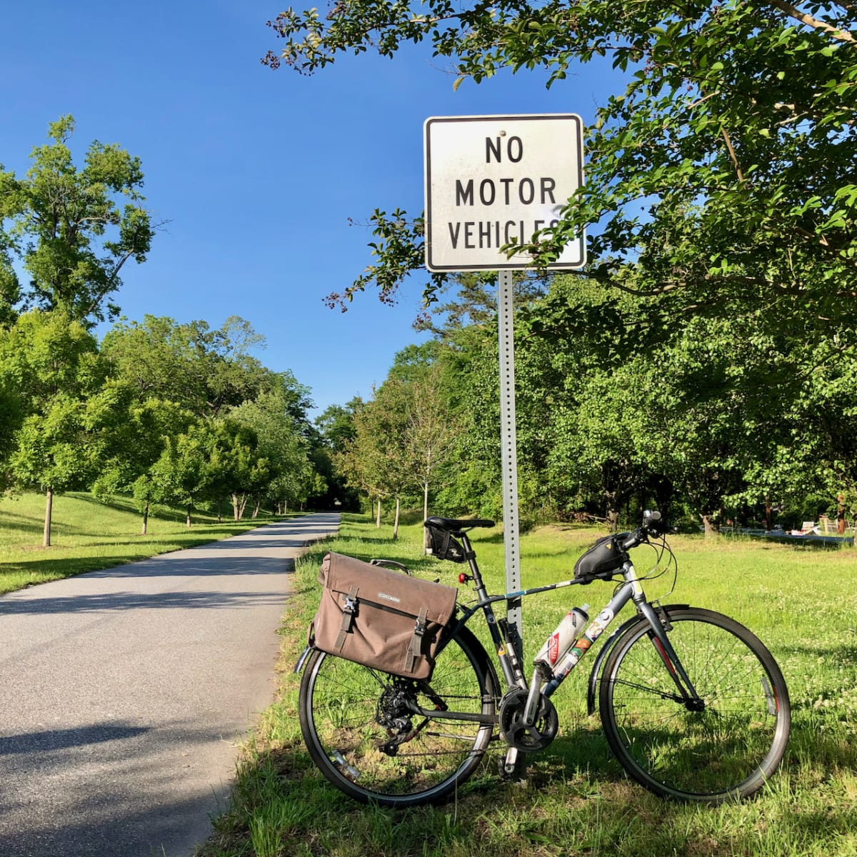 """A photo of my bicycle in front of a """"no motor vehicles"""" sign beside a trail."""