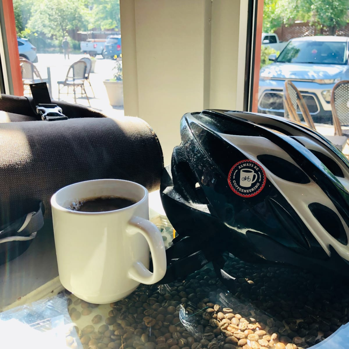 A photo of a coffee cup on a table beside a bicycle helmet.