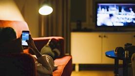 סמארטפון ביד מול מסך הטלוויזיה, צילום: iStock
