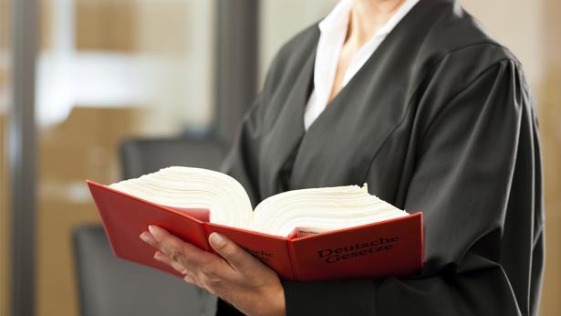 """עו""""ד אוחזת בספר החוקים הגרמני, צילום: גטי אימג'ס"""