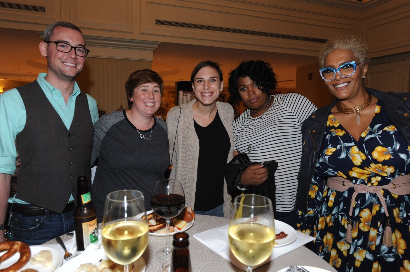 Group of 5 people standing around a table. Their arms are around each other, and there are wine glasses, beer bottles, and plates of food on the table.
