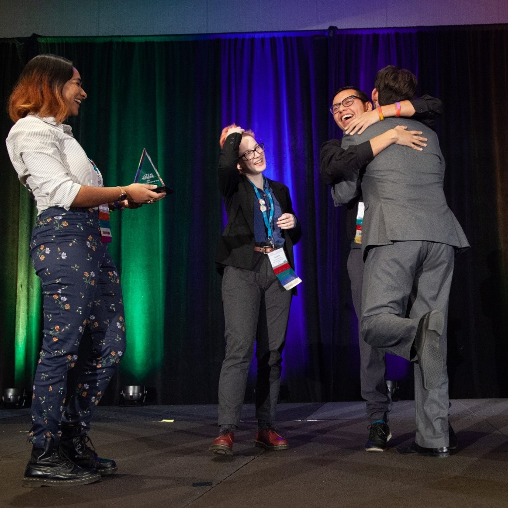 An award being presented as awardees hug on stage