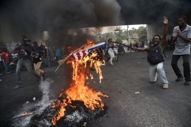 A protestor burns a U.S. flag at demonstration in Port-au-Prince