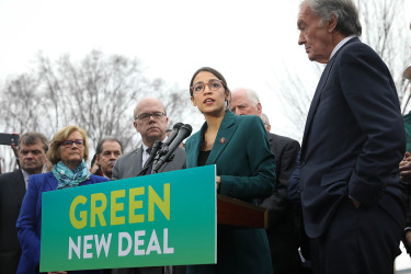 Representative Alexandria Ocasio-Cortez (center) speaks on the Green New Deal with Senator Ed Markey (right) in front of the Capitol Building in February 2019.