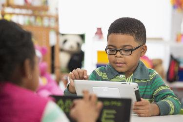 Black kid calculating on iPad.