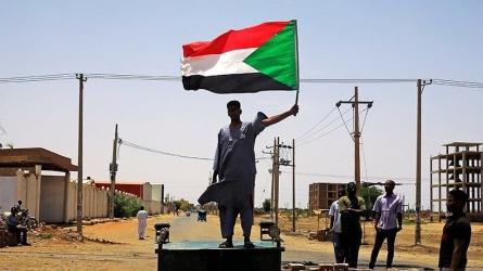 Man holding the Sudanese flag.