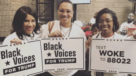 Black attendees hold signs that say 'Black voices for Trump'