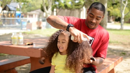 Dad doing daughter's hair.
