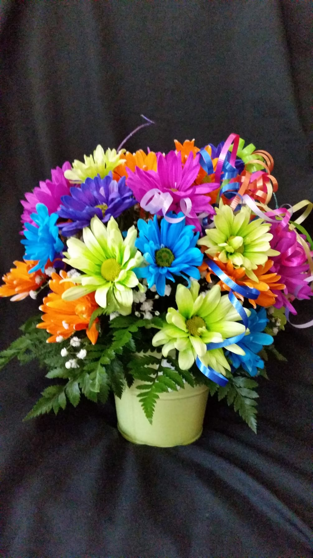 This fun flower arrangement is filled with neon colored daisies. It will