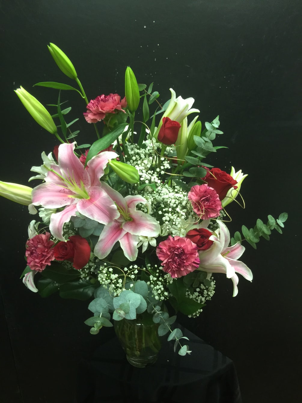 Pink Lilies Roses Eucalyptus And Filler Flowers Arranged In A