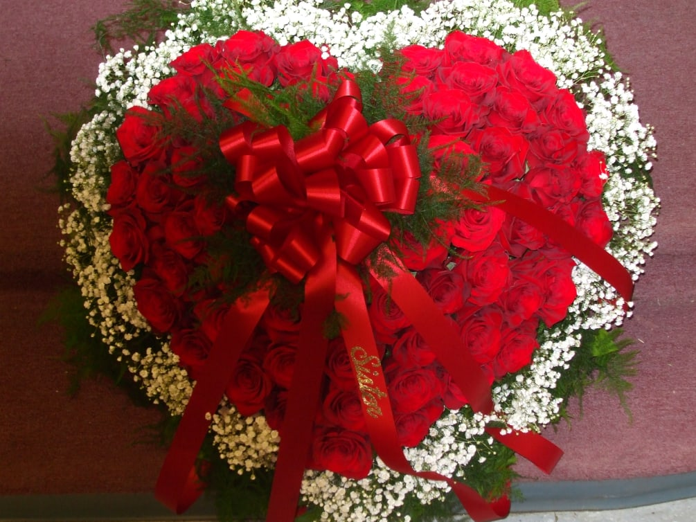 A glorious heart shaped easel arrangement created with beautiful red roses and