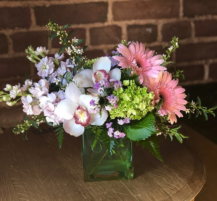 Beautiful pinks and greens displayed with hydrangea, gerbera daisies, cymbidium orchids and