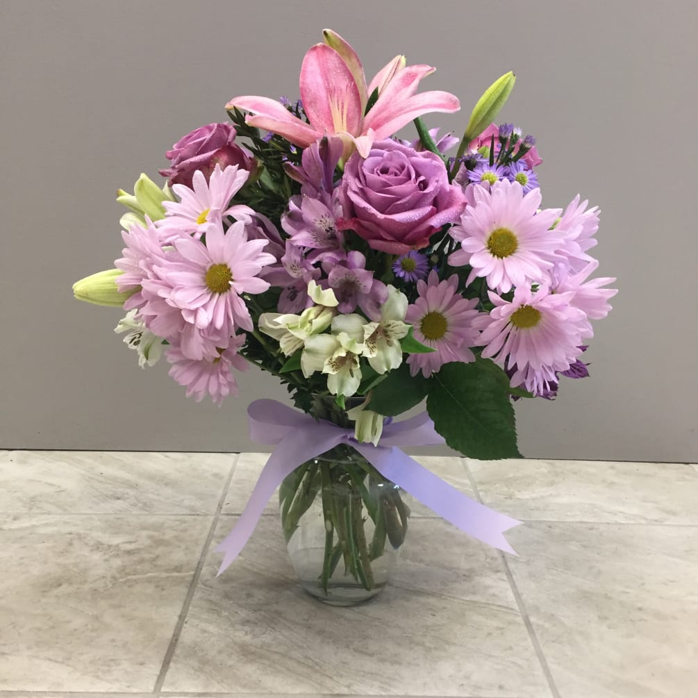 purple, lavender and pink mixed flowers in a clear glass bud vase