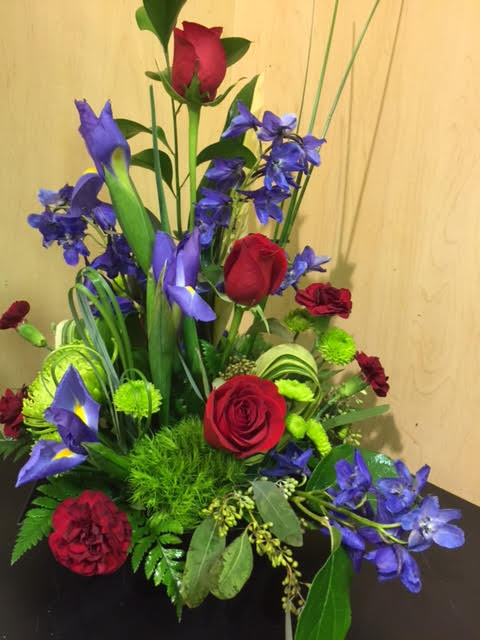 Roses, carnations, iris, spider mums, mixed greenery and leaves