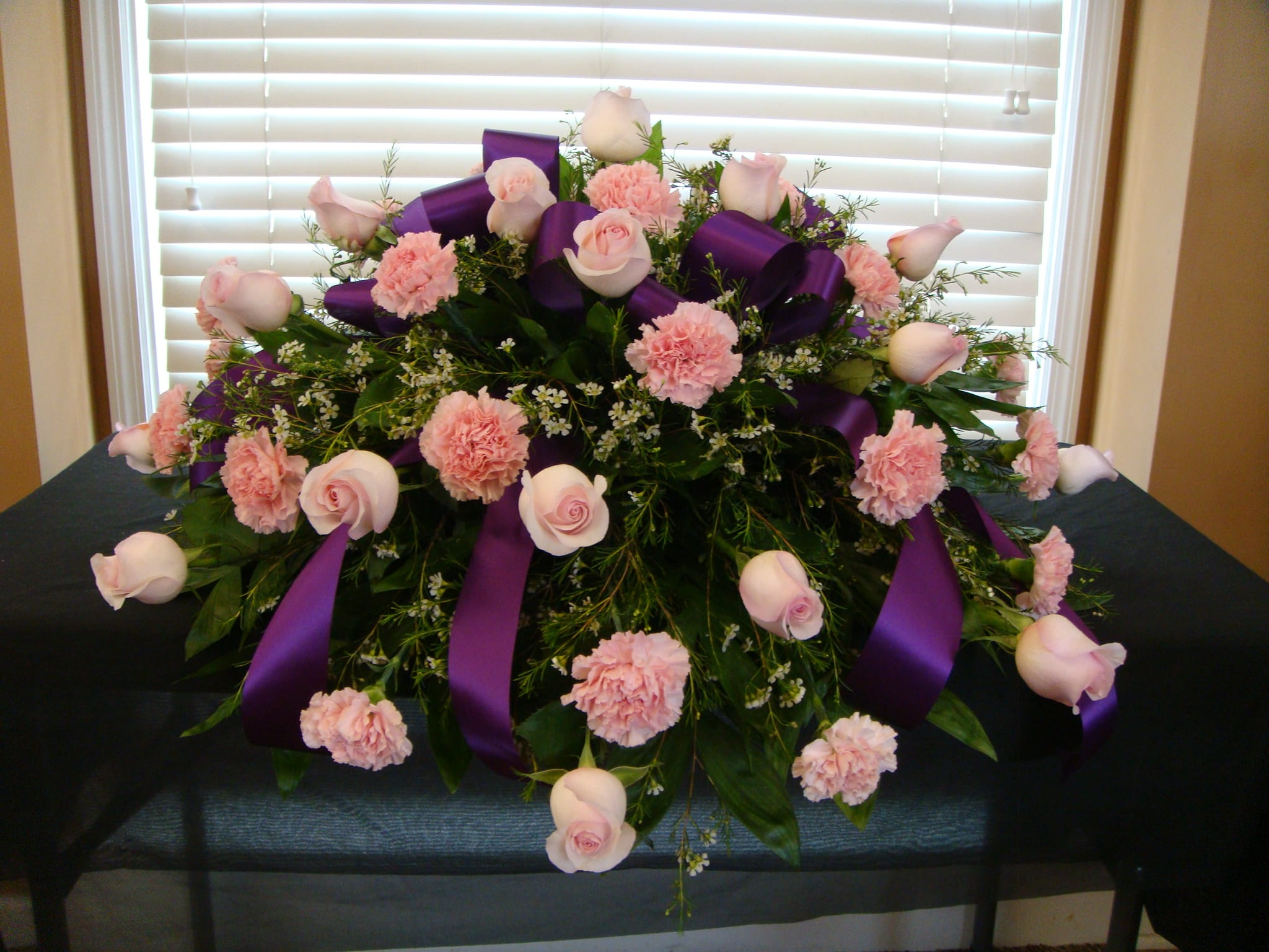 Casket cover in pinks with purple ribbon
