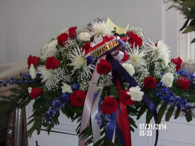 Red roses, white spider mums, white carnations and blue delphinium make a