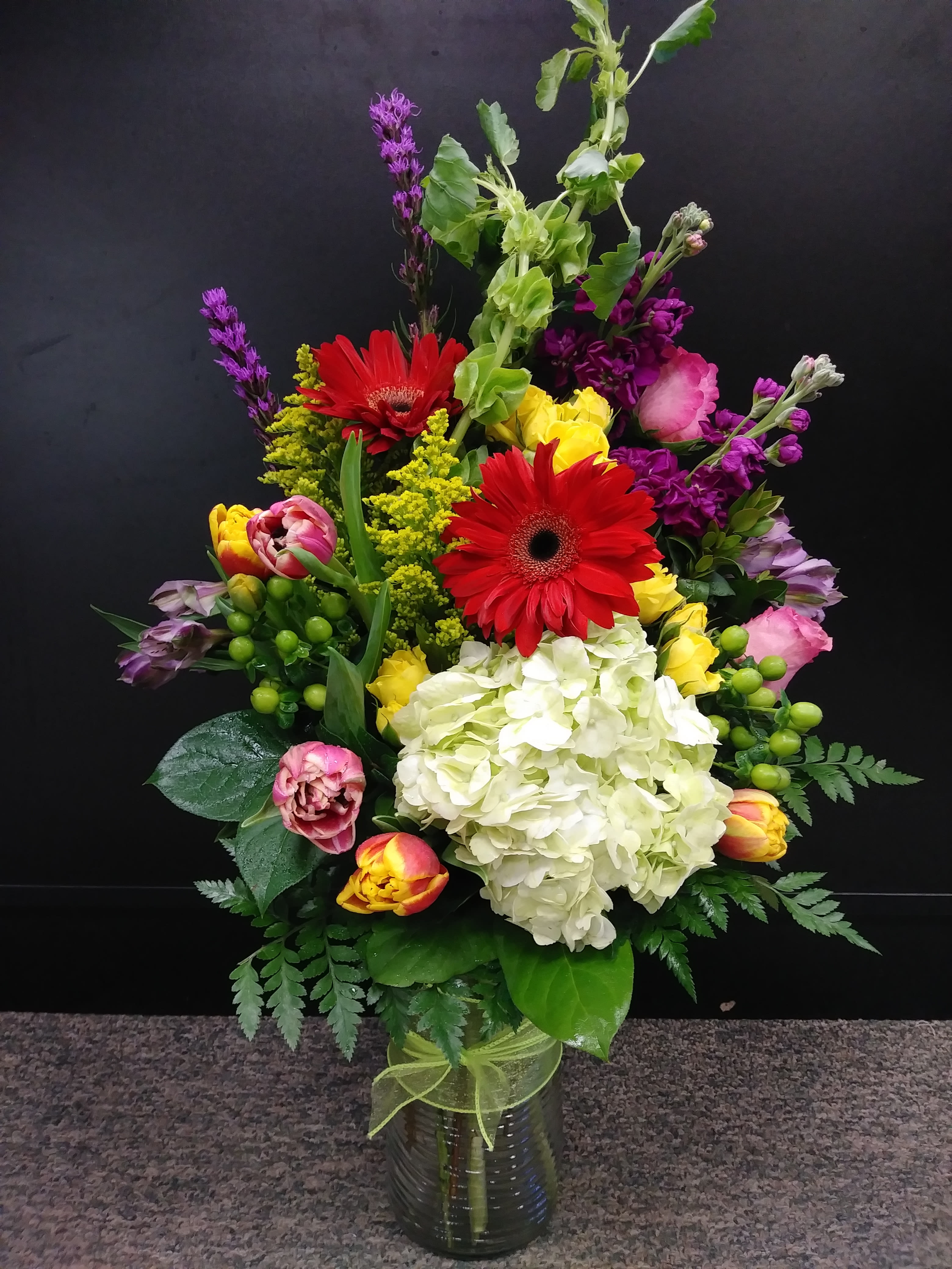 Joyful wishes - A lovely vase arrangement of cheerful spring flowers sure to bring sunshine to