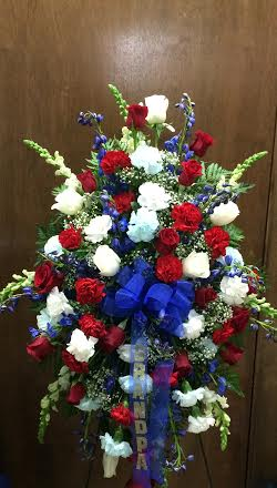 standing easel spray with white snaps, red and white roses, blue delphinium