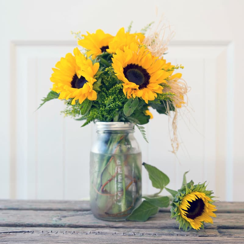 Mason Jar With Curly willow accents, Sunflowers and Solidago. Raffia Bow