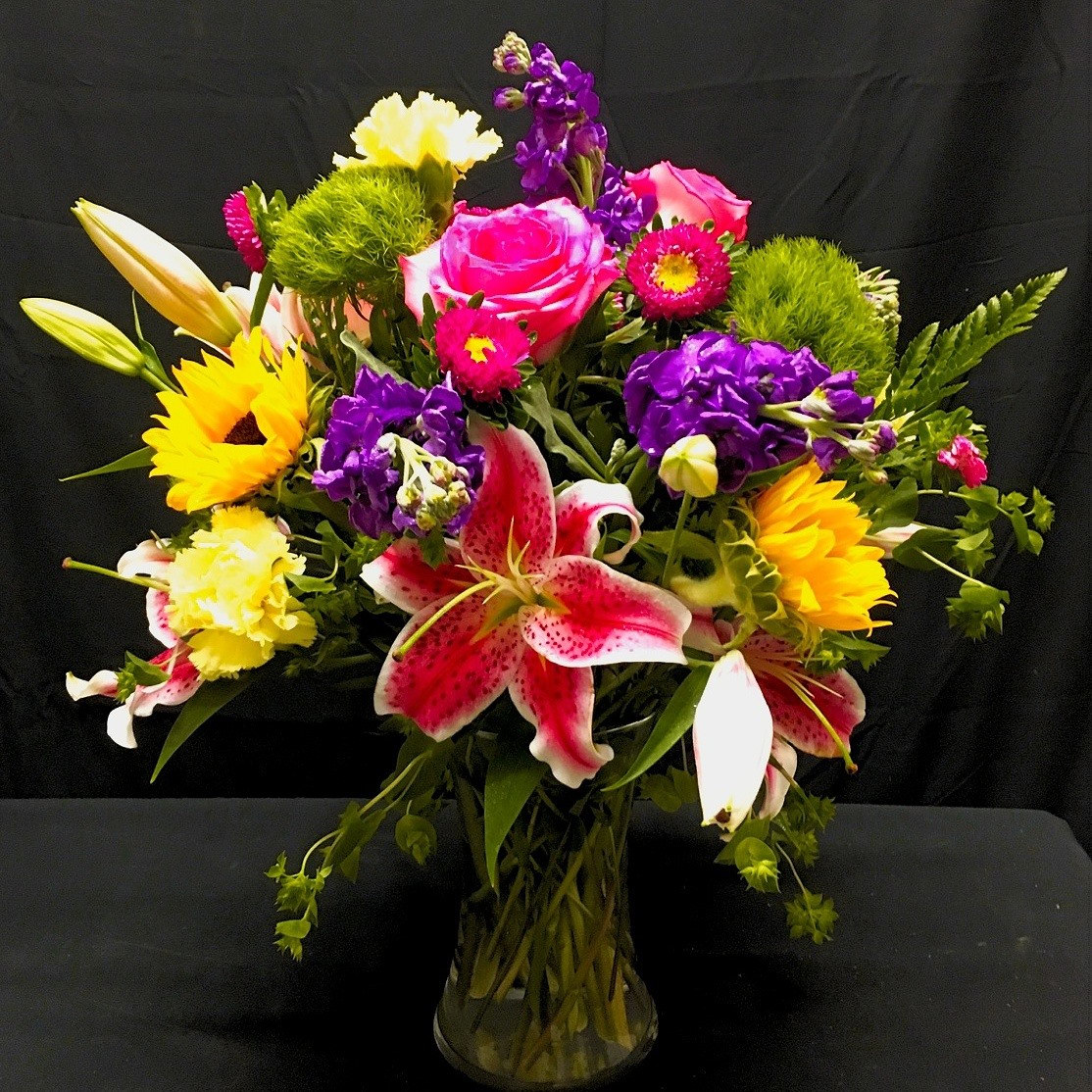Sun & Stars - Stargazer Lilies & Sunflowers highlight this fresh floral arrangement. Accented by
