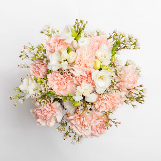 A bouquet of peach carnations, white wax flowers and white freesia. Stems