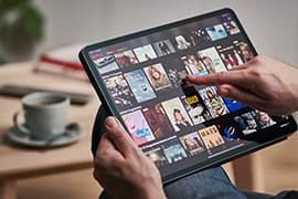 A hand scrolling through Netflix on a tablet device