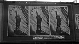 Photo of large posters on a wall with text saying 'Liberation'