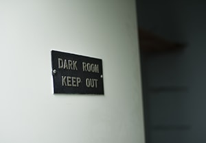 'Dark Room Keep Out' sign on brick wall