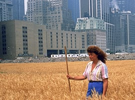American environmental and conceptual artist Agnes Denes photographed standing in her installation, a two-acre wheat field with a city-scape in the background