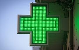 Lit up green cross sign attached to a wall