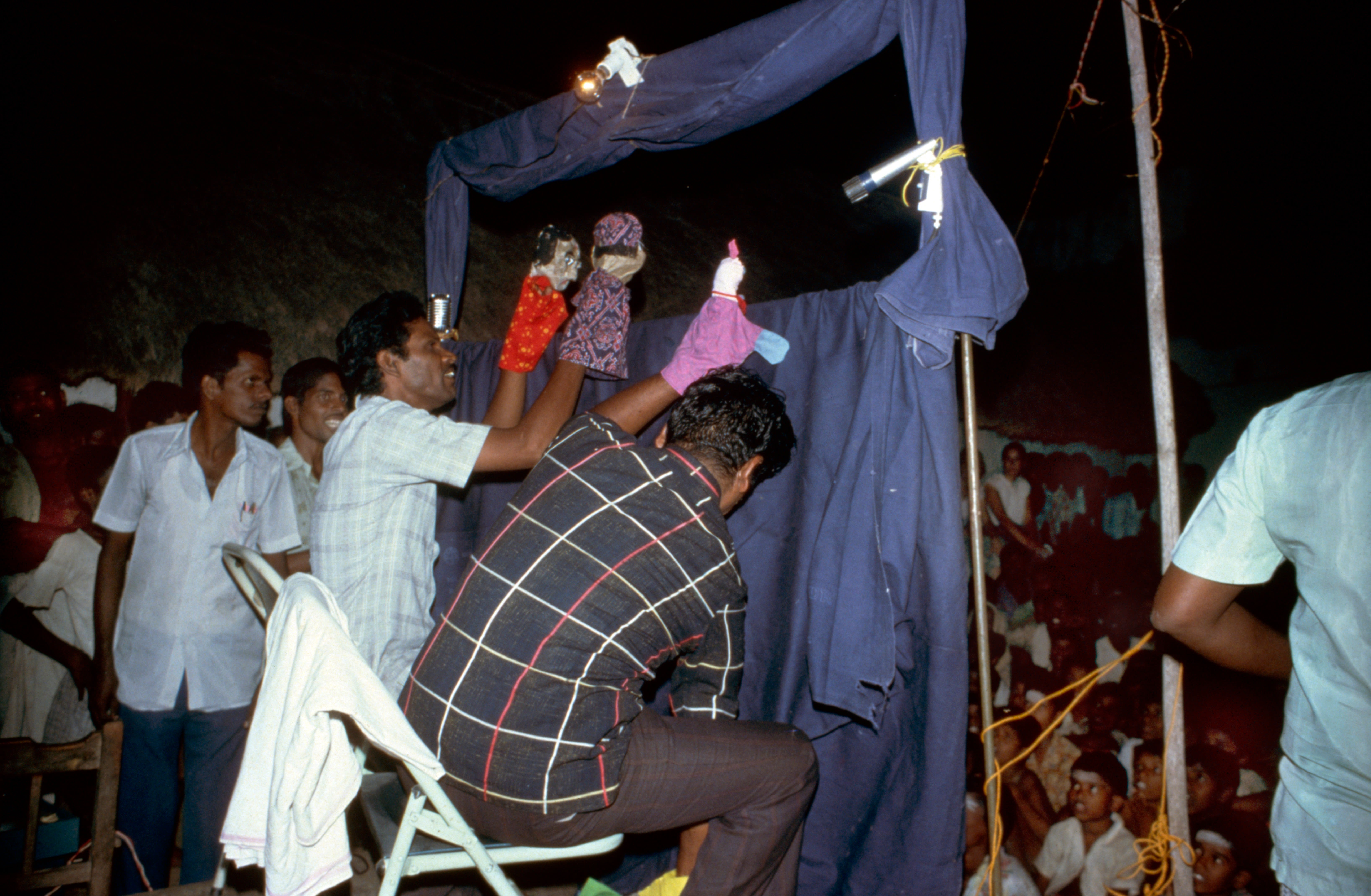 Image showing primary health care workers giving a puppet show to a group of people in a village in India